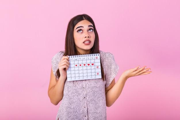 Giovane donna che tiene il calendario femminile periodi per il controllo dei giorni delle mestruazioni
