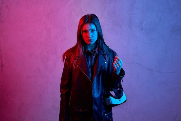 Giovane donna che tiene il casco di realtà virtuale mentre indossa una giacca