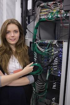 Giovane donna che tiene il cavo usb davanti ai server