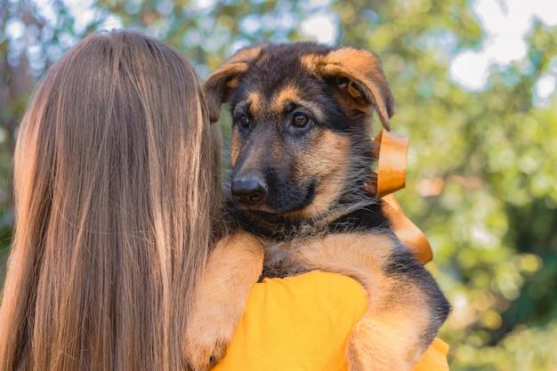 Giovane donna che tiene il suo cucciolo di pastore tedesco sulla spalla