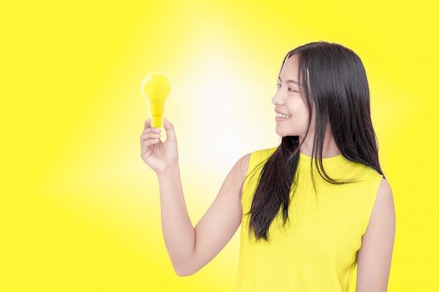 Giovane donna che tiene lampadina gialla.