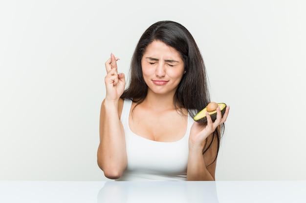 Giovane donna che tiene le dita di un incrocio di avocado per avere fortuna