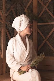 Giovane donna che tiene le erbe mediche che si rilassano nella sauna