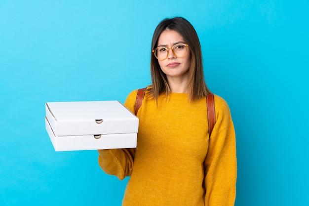 Giovane donna che tiene le scatole di una pizza sopra la parete blu isolata