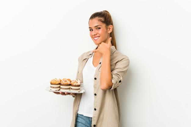 Giovane donna che tiene le torte dolci che mostrano un gesto di chiamata di telefono cellulare con le dita