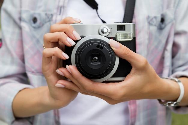 Giovane donna che tiene nella vecchia macchina fotografica d'annata delle mani.