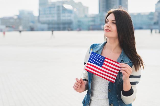 Giovane donna che tiene piccola bandiera americana durante la celebrazione della festa dell'indipendenza