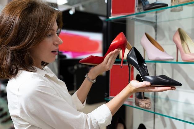 Giovane donna che tiene scarpa con tacco nera e scarpa con tacco rossa in negozio