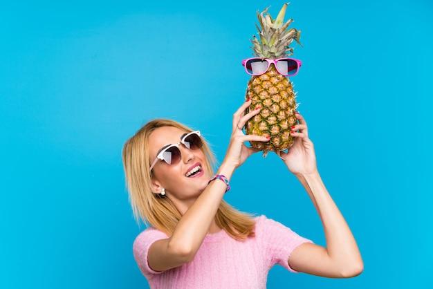 Giovane donna che tiene un ananas con gli occhiali da sole