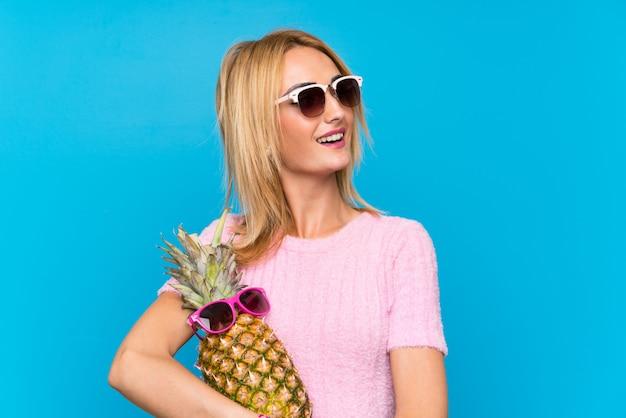 Giovane donna che tiene un ananas con occhiali da sole