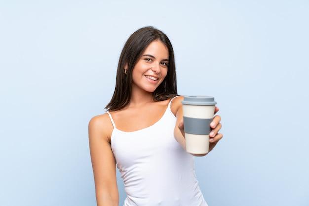 Giovane donna che tiene un caffè da asporto sopra la parete blu isolata