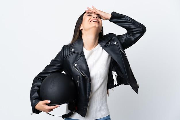 Giovane donna che tiene un casco del motociclo sopra la risata bianca isolata della parete