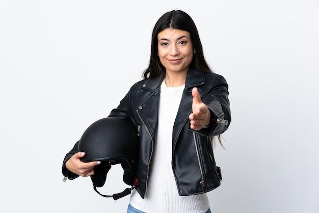 Giovane donna che tiene un casco del motociclo sopra la stretta di mano isolata della parete bianca dopo il buon affare