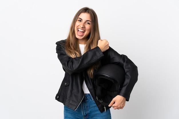 Giovane donna che tiene un casco del motociclo su bianco isolato che celebra una vittoria