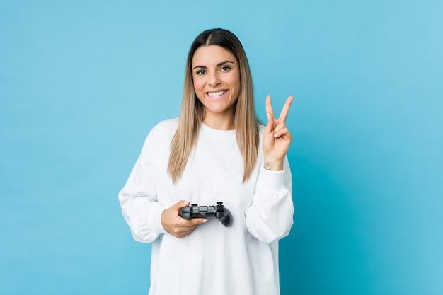 Giovane donna che tiene un controller di gioco che mostra il numero due con le dita.