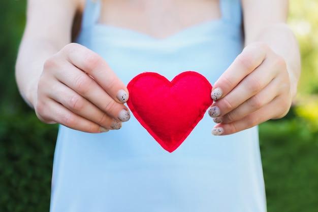 Giovane donna che tiene un cuore rosso nelle sue mani