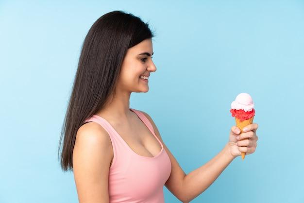 Giovane donna che tiene un gelato della cornetta sopra la parete blu isolata con l'espressione felice