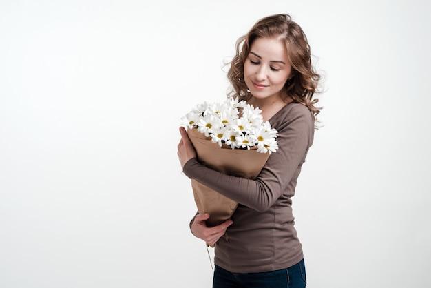 Giovane donna che tiene un mazzo di margherite bianche. muro bianco.