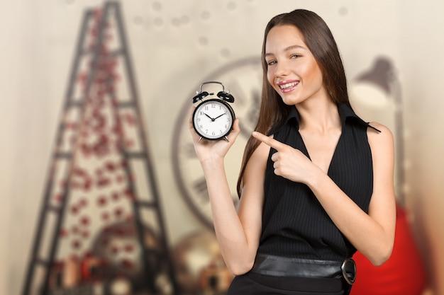 Giovane donna che tiene un orologio. concetto di gestione del tempo