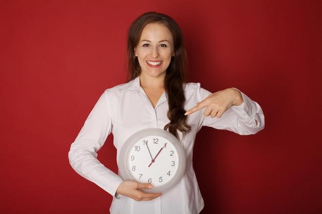 Giovane donna che tiene un orologio su un rosso.
