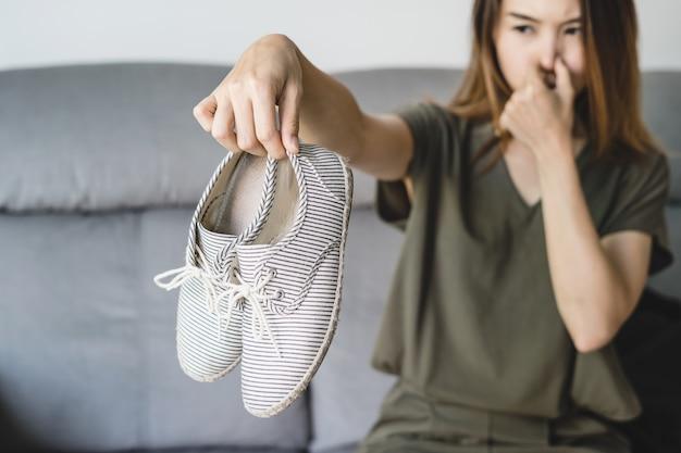 Giovane donna che tiene un paio di scarpe puzzolenti
