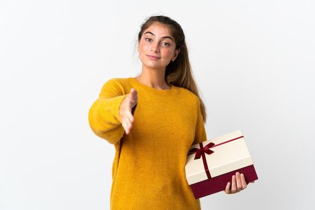 Giovane donna che tiene un regalo isolato su bianco stringe la mano per chiudere un buon affare