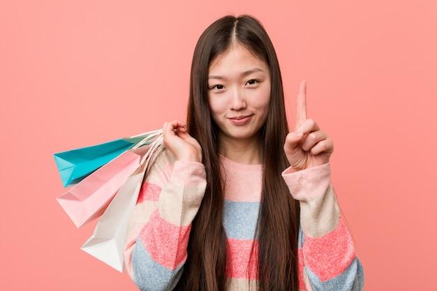 Giovane donna che tiene un sacchetto della spesa che mostra numero uno con il dito.