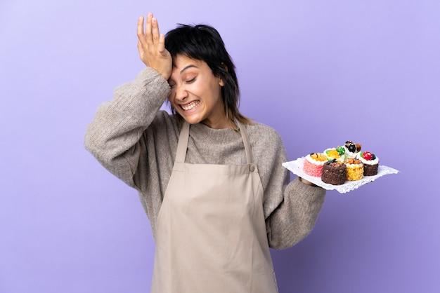 Giovane donna che tiene un sacco di mini torte diverse sul muro viola con dubbi con espressione del viso confuso