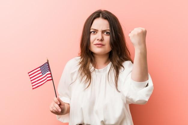Giovane donna che tiene una bandiera degli stati uniti che mostra pugno