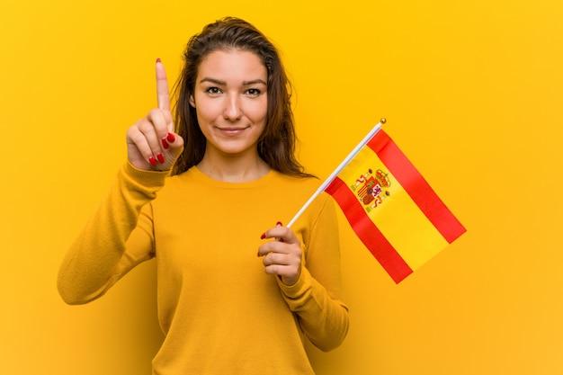 Giovane donna che tiene una bandiera spagnola che mostra numero uno con il dito