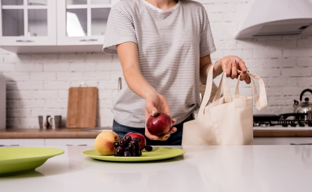 Giovane donna che tiene una borsa di stoffa. in cucina. non sono di plastica. campagna per ridurre l'uso di sacchetti di plastica. zero sprechi