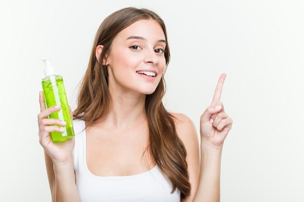 Giovane donna che tiene una bottiglia di vera dell'aloe che sorride allegramente indicando con l'indice di distanza