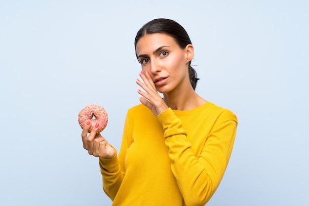 Giovane donna che tiene una ciambella sopra la parete blu isolata che bisbiglia qualcosa