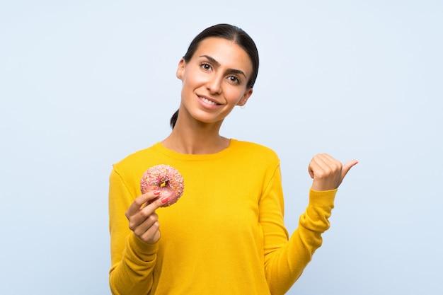 Giovane donna che tiene una ciambella sopra la parete blu isolata che indica il lato per presentare un prodotto