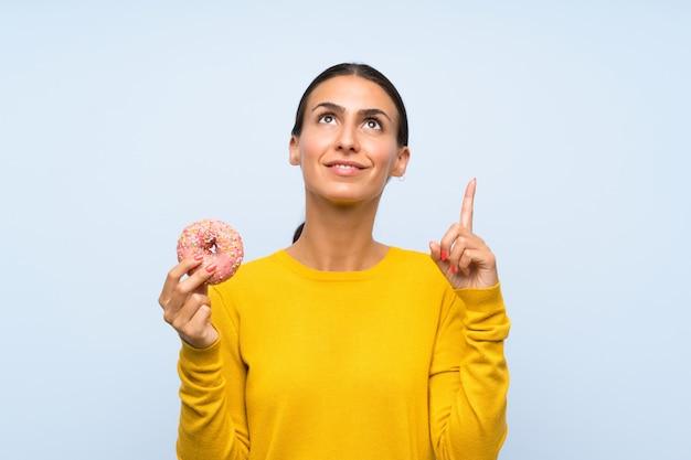 Giovane donna che tiene una ciambella sopra la parete blu isolata che indica su una grande idea