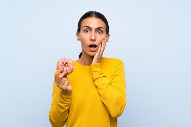 Giovane donna che tiene una ciambella sopra la parete blu isolata con espressione facciale sorpresa e colpita