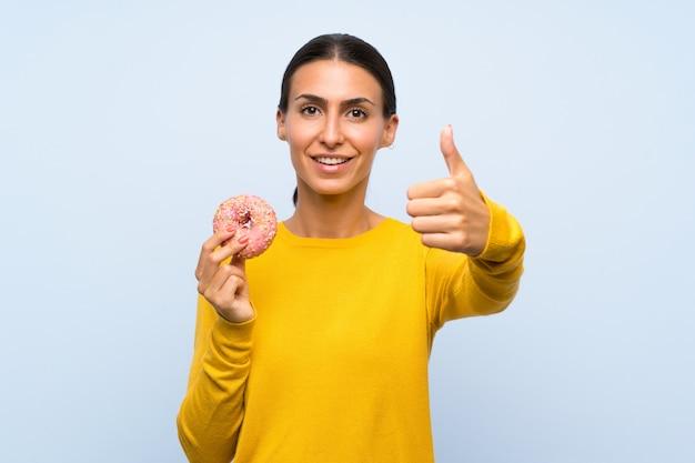 Giovane donna che tiene una ciambella sopra la parete blu isolata con i pollici in su perché è successo qualcosa di buono