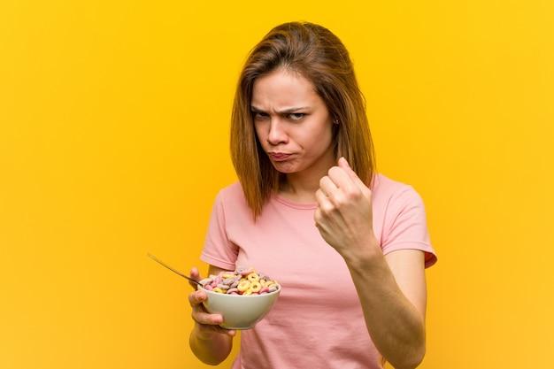 Giovane donna che tiene una ciotola di cereali che mostra pugno alla macchina fotografica, espressione facciale aggressiva.