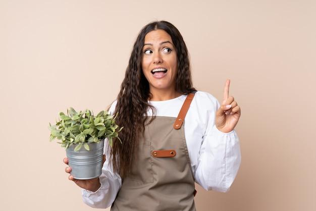 Giovane donna che tiene una pianta che intende realizzare la soluzione sollevando un dito