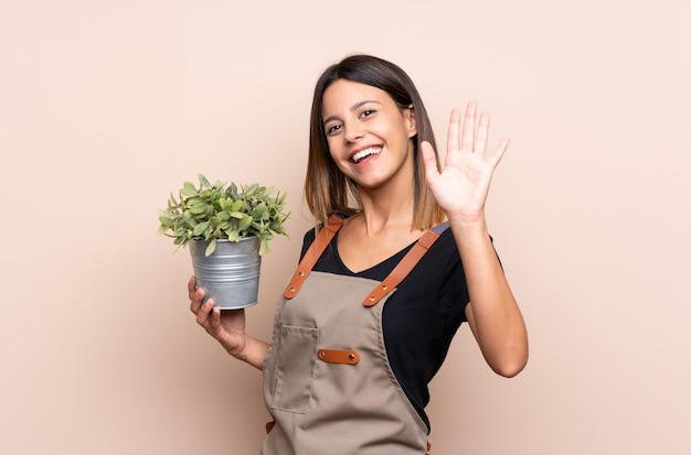Giovane donna che tiene una pianta che saluta con la mano con l'espressione felice