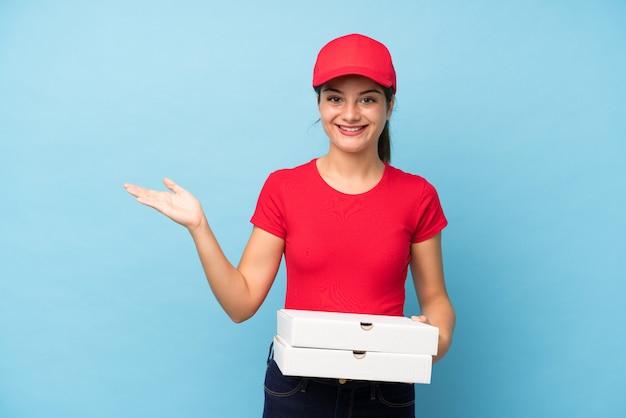 Giovane donna che tiene una pizza sopra il copyspace rosa isolato della tenuta della parete immaginario sulla palma