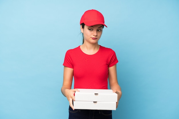 Giovane donna che tiene una pizza sopra la parete rosa isolata che pensa un'idea