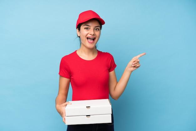 Giovane donna che tiene una pizza sopra la parete rosa isolata sorpresa e che indica dito il lato