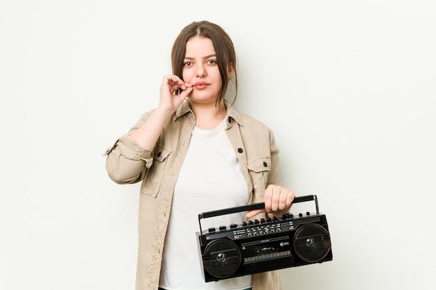 Giovane donna che tiene una radio retrò con le dita sulle labbra mantenendo un segreto.