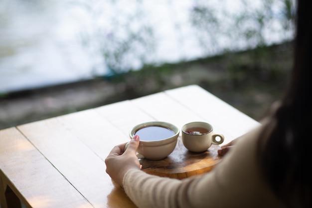 Giovane donna che tiene una tazza di caffè caldo nella vista della natura