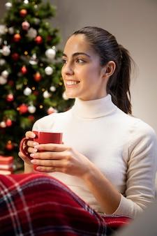 Giovane donna che tiene una tazza rossa