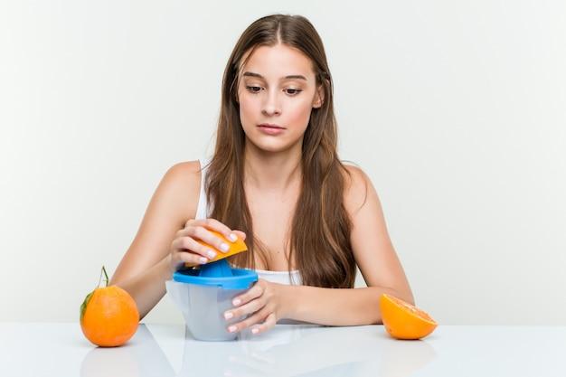 Giovane donna che tiene uno spremiagrumi arancione