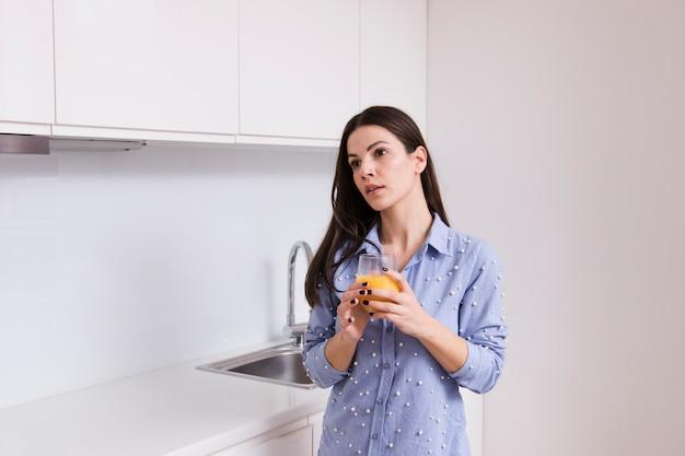 Giovane donna che tiene vetro di succo in piedi in cucina