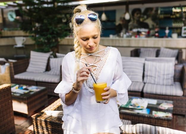 Giovane donna che tiene vetro di succo mescolando con paglia
