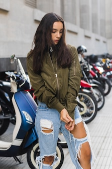 Giovane donna che tira le maniche della giacca